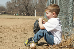 Preschool boy sitting with ball and glove Stock Photos