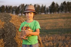 Boy with basket of buns. In the background of haystacks in a field Royalty Free Stock Photography