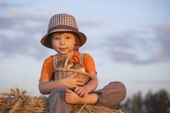 Boy with basket of buns. In the background of haystacks in a field Stock Photo