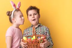 A boy with a basket of painted eggs and a girl with ears of a hare. On a yellow background stock photography