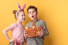 A boy with a basket of painted eggs and a girl with ears of a hare. On a yellow background stock photos