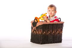 Boy in basket with toy Royalty Free Stock Image