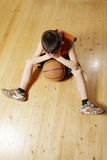 Boy with basketball on floor Royalty Free Stock Image