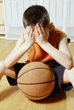 Boy with basketball on floor closeup Royalty Free Stock Photos