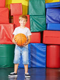 Boy with basketball in gym Stock Images