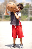 Boy with basketball on his shoulders. Outdoors Stock Photos