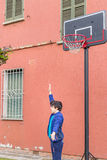 Boy in a basketball playground. Boy training defensive positions in a basketball grunge playground near the peeling wall of an old house stock photography