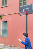 Boy in a basketball playground. Boy training defensive positions in a basketball grunge playground near the peeling wall of an old house royalty free stock photography