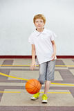 Boy with basketball in schoolyard Stock Image