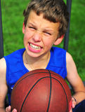 Boy with a basketball sitting on court Stock Images