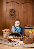 Boy among baskets with vegetables Stock Photography