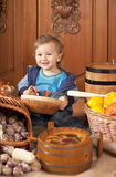Boy among baskets with vegetables Stock Images
