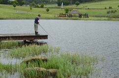 Boy bass fishing on dam or lake pier Stock Images