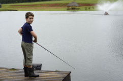 Boy bass fishing on dam or lake pier Stock Photos