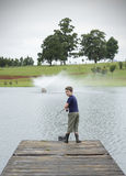 Boy bass fishing on lake pier Stock Images