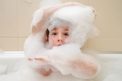 Boy in a bath with foam. Boy (10-11) in a bath covered with foam Royalty Free Stock Images