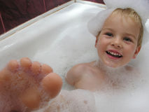 Boy in bath with leg Stock Photography