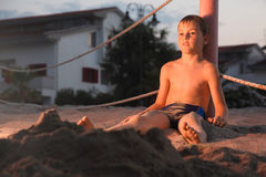 Boy after bath sits in sand on beach Royalty Free Stock Photos