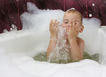 Boy in bath with splash of water. In hands stock photo