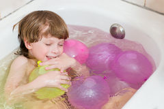 Boy bathes in a bathroom with balloons Royalty Free Stock Photo