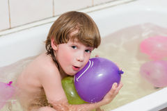 Boy bathes in a bathroom with balloons Royalty Free Stock Images