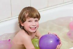 Boy bathes in a bathroom with balloons Stock Photos