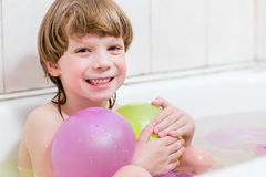 Boy bathes in a bathroom with balloons Stock Image