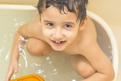 Boy bathes in the tub. Boy with brown eyes bathes alone in the tub and looks at the camera stock photography