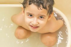 Boy bathes in the tub. Boy with brown eyes bathes alone in the tub and looks at the camera royalty free stock photo