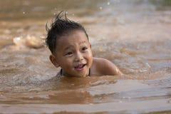 The boy bathes in water. stock photos
