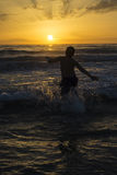 Boy bathing on the beach at dusk Royalty Free Stock Photo