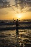Boy bathing on the beach at dusk Stock Photos