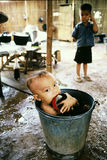 Boy bathing in a bucket. Hmong child having bath at refugee camp in Thailand Royalty Free Stock Photo