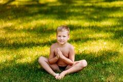 Boy Yogi sits on green grass royalty free stock images