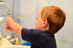 Boy in the bathroom. Little boy washing his hands  in the bathroom early in the morning Stock Image