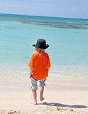 Boy on beach. Boy on tropical beach protecting himself from the sunlight with a hat Stock Photos