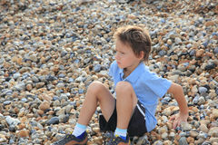 Boy on the beach. Little boy sitting on the pebble beach Stock Photography