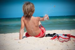 Boy on beach. Rear view of young boy on sandy beach next to snorkel, sea in background stock images