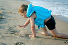 The boy on the beach. The boy crawls ashore from the sea, very utavshy, but very happy Royalty Free Stock Photos