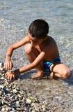 Boy on beach. Plays sea stone Stock Photos