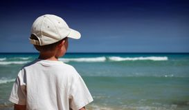 Boy on the beach. Boy in white shirt watches the waves on the beach Stock Image