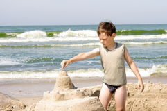 Boy on a beach. Boy is concentrated on his work on the beach Stock Image