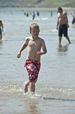 Boy on the beach. An image of a young boy wearing boardshorts running through the water on a hot summers day stock photography
