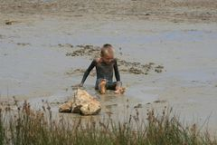 Boy on the beach. Boy sitting on the beach in healthy mud Royalty Free Stock Images