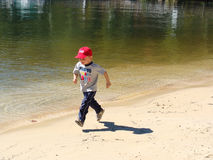 Boy on the beach. Young boy running on the lake shore Royalty Free Stock Photography