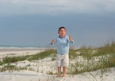 Boy on the beach. Young boy standing on the beach looking up and raising his hands to the heaven Stock Photography