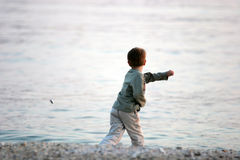 Boy at the Beach. Boy throwing stones into the sea Stock Image