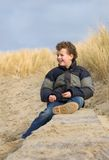Boy on Beach. Boy (7) on a beach, sitting on a wooden beam against some dunes Royalty Free Stock Photo