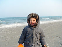 Boy on Beach. Smiling 2 year old boy standing on a beach at seaside wearing a heavy jacket with hood stock photography