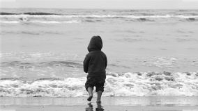 Boy on beach. A black and white photo of a young boy on a sandy beach and open sea in the background Royalty Free Stock Photos